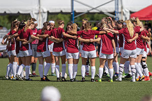 A photo of the Regis Women's Soccer Team in a huddle