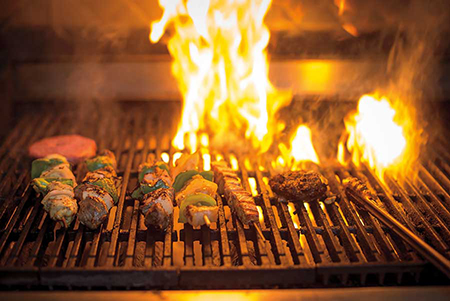 Food cooking on the grill with flames in the background