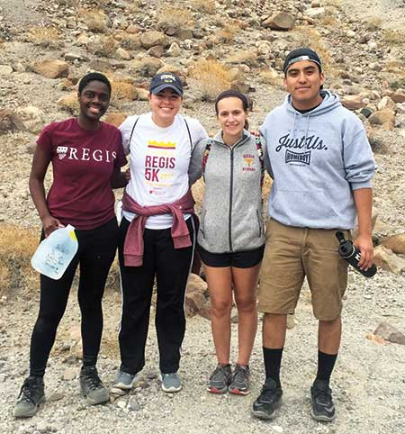 Four Regis students posing in front of a hill in the desert
