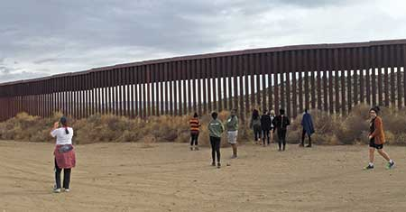 People dwarfed by the border wall in Jucumba Hot Springs, CA