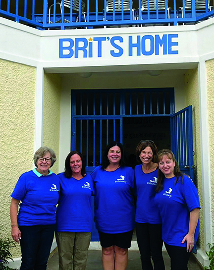 Susan Sawyer, Sheryl Kelleher, Lisa Krikorian, Kimberly Campbell, and Cherylann Gengel pose in front of the door to Brit's Home with the sign visible above them.