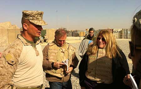 Giacomo, wearing a flak jacket, talks with a soldier in full gear in the Afganistan desert