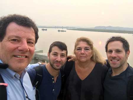 Nick Kristof, Jonah Kessel, Carol Giacomo, and Adam Ellic pose with a lake in the background