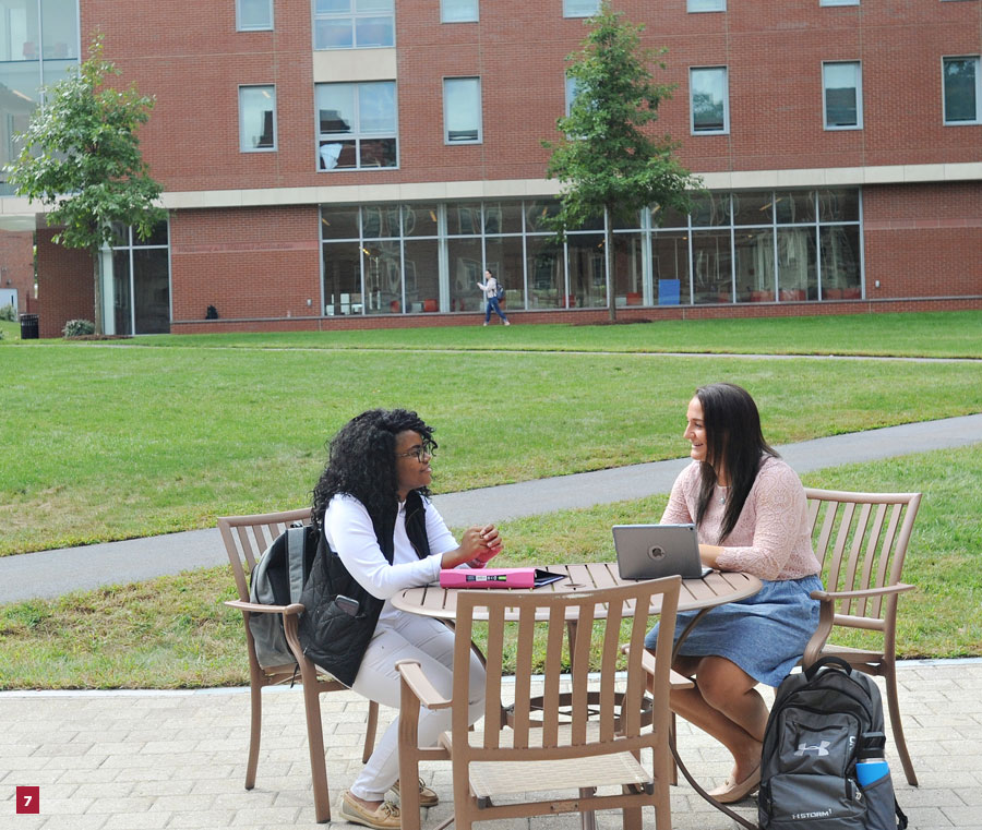 7) photo of two students sitting at a table in the Luben Plaza qith the Quad in the background