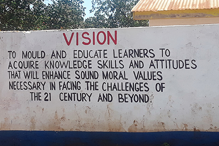 Photo of a sign reading: Vision To mould and educate learners to acquire knowledge skills and attitudes that will enhance sound moral values necessary in facing the challenges of the 21 century and beyond.